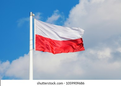 Polish national flag waving on the wind against blue cloudy sky