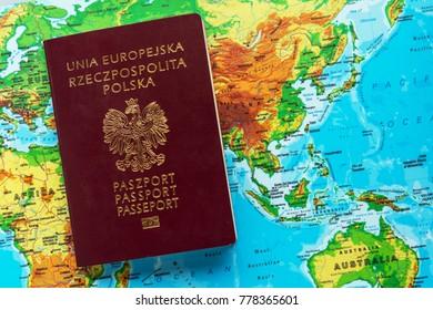 Polish passport of citizen against the continent of Australia. Poles immigration to Australia concept.