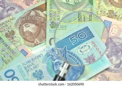 polish zloty banknotes under magnifying glass