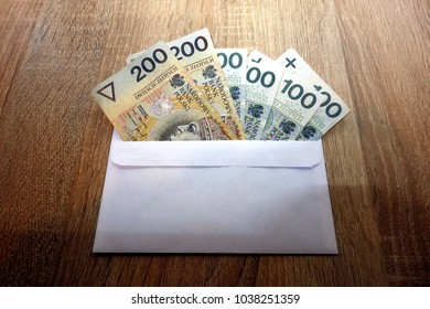 Polish zloty currency money in envelope on desk, bribe concept