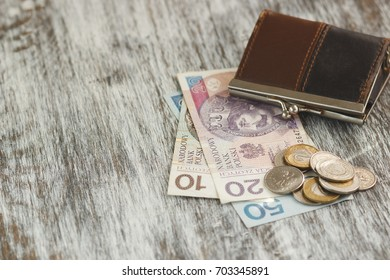 Polish zloty with little wallet on the old wooden background, soft focus background