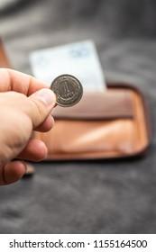 Polish Zloty (PLN) on hand. 1(one) Polish zloty on brown wallet.
