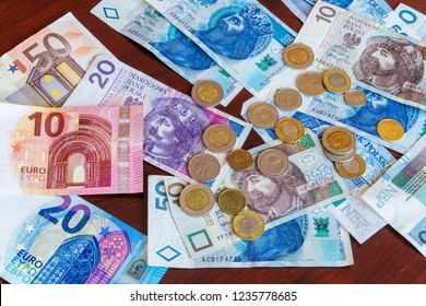 Polish zloty - zl money banknotes and coins with euro banknotes. Official currency of Poland in denominations of 10, 20 & 50 zloty bills with groszy coins on table next to 10, 20 & 50 euro bills.