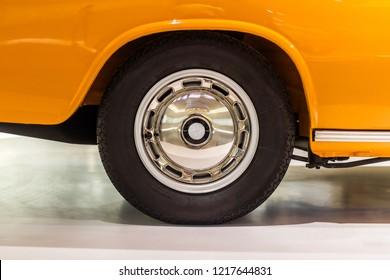 Polished car rim with black vintage wheel on orange car with studio light in Germany