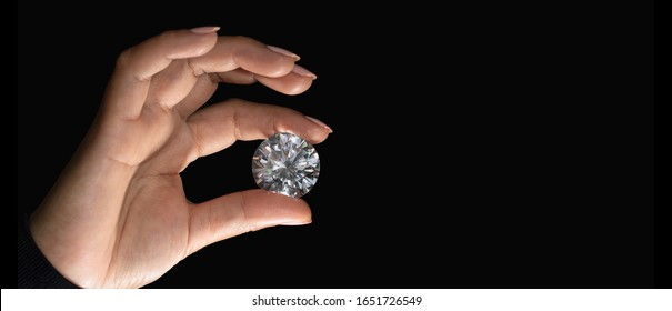 Polished diamond in a female hand on a black background. Concept for jewellery business on a banner.