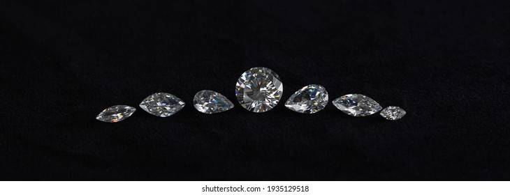 Polished diamonds of different cuts are laid out in a row. Seven diamonds in form of necklace on black velvet banner.