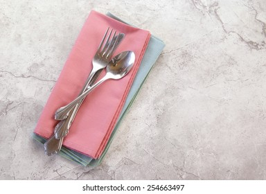 Polished metal tableware casually arranged on cloth mint and coral napkins lay on a white marbled counter or table with a top down perspective and copyspace.