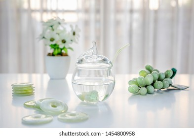 Polished small jade stones are located inside of a glass jar with crystalline water. It is making crystal charged water at home. There are donuts carved grapes and white flowers on the table.