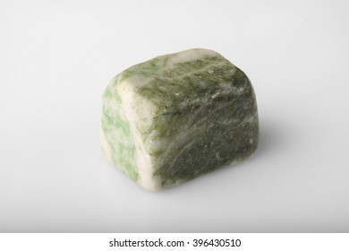 Polished stone green jadeite on a gray background.