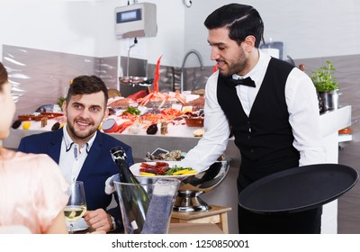 Polite attractive waiter bringing ordered seafood dishes to smiling couple at fish restaurant
