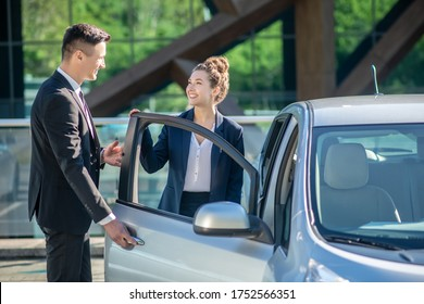 Polite behavior. Polite young man in a suit opening a car door for a pretty smiling woman.