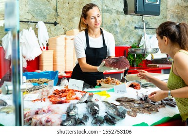 Polite diligent positive  female fishmonger standing behind counter of seafood store demonstrating raw bonito steak to woman buyer