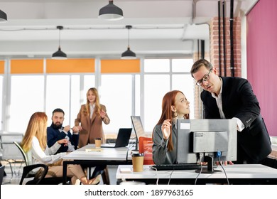polite director gives directions and advice to his employee working at the computer in the office, successful team