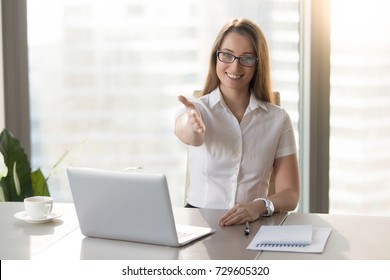 Polite friendly businesswoman extending hand at camera, smiling woman offering handshake while sitting at workplace in office, open to cooperation, greeting partner, welcoming at job interview
