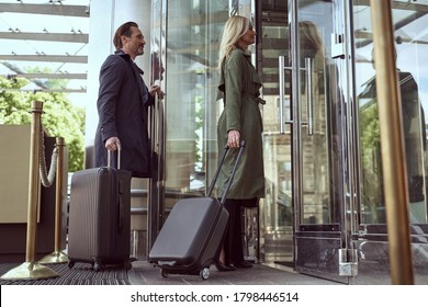 Polite man in a travel jacket waiting for a beautiful woman in to enter a hotel while propping the door open