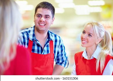 polite supermarket staff serves customer