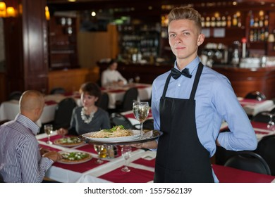 Polite waiter holding tray in restaurant with customers behind him
