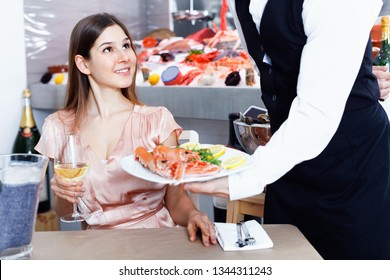 Polite waiter serving ordered seafood dishes to attractive cheerful  smiling girl at fish restaurant