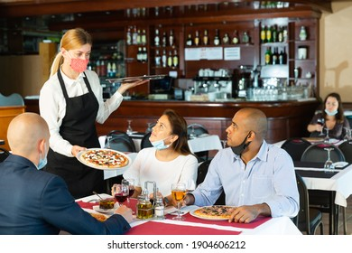 Polite waitress in protective mask bringing ordered pizza to friends visited restaurant for lunch