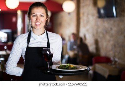 Polite waitress wearing apron holding tray with dishes in restaurant interior