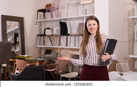 Polite woman seller consulting customers in furniture shop, standing with folder