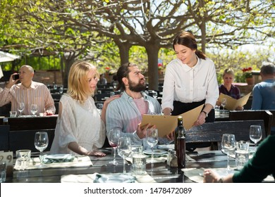 Polite young waitress showing menu card to smiling couple, recommending dishes in cosy country restaurant in open air