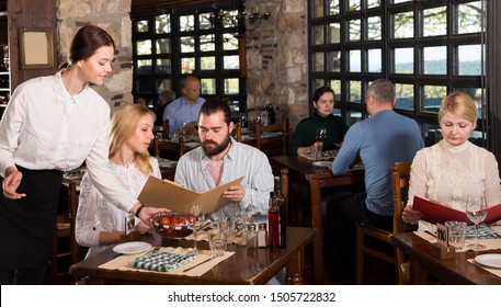 Polite young waitress showing menu card to couple, recommending dishes in cosy country restaurant