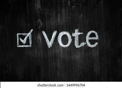 """Political activism sign: handwritten word """"vote"""" in black background. Election process concept: word vote and an filled-in tick box in wood low-key background"""