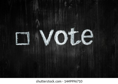 """Political activism sign: handwritten word """"vote"""" in black background. Election process concept: word vote and an empty tick box in wood low-key background"""