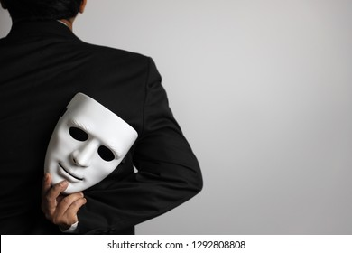 politician or businessman wearing black suit and hiding white mask