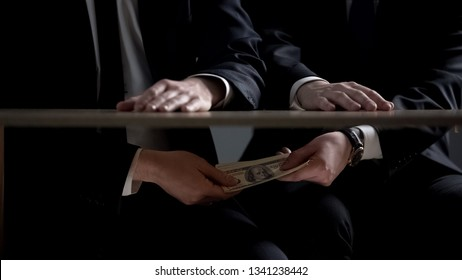 Politician hands taking bribe money under office table, lobbying of interests