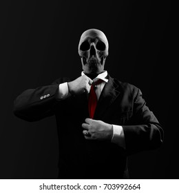 Politician with skull. Black and white politician man with skull head in black suit straightens a red tie on black background.
