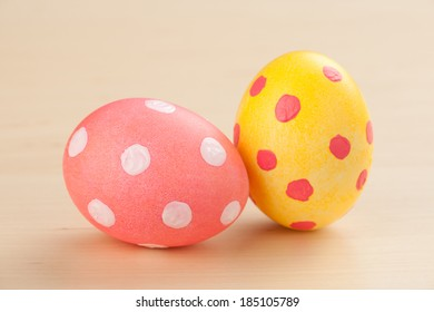 Polka dot painted Easter Eggs on light wooden table top.