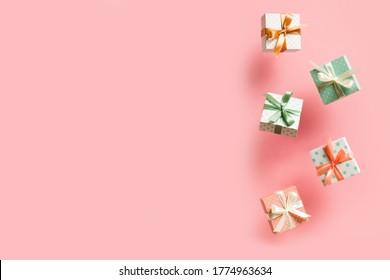 Polka dot pattern gift box with ribbon falling on pink background, levitation, creative pastel