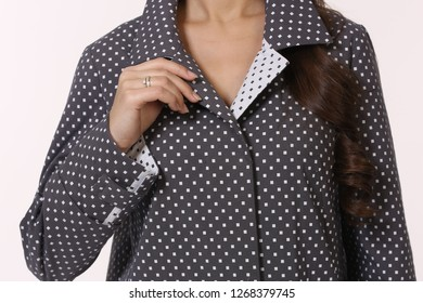 polka dot trench coat close up photo with model hand hold collar isolated on white