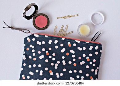 Polka dotted girl makeup bag, golden hairpins, lip balm and pink blusher on the table