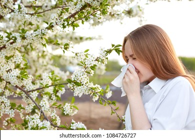 Pollen allergy symptom. Sideways outdoor shot of young European female sneezes in handkerchief or blows in wipe , being allergic to blossom during spring, stands on front of blooming tree outside.