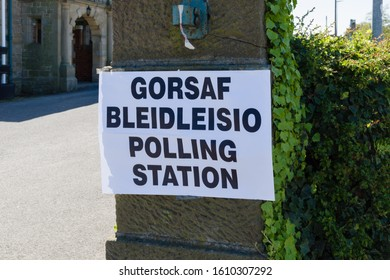 Polling station sign in Welsh and English language showing where people can go to cast their vote in an election in Wales UK