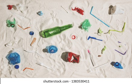 Polluted beach with plastic, glass waste and assorted rubbish: environmental protection and plastic pollution concept