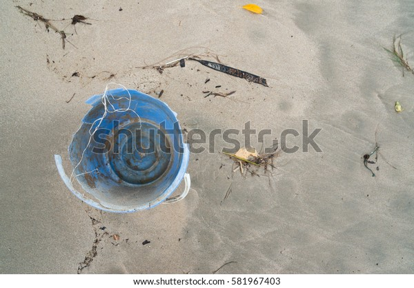 Polluted beach shore. Plastic abandoned on sand.