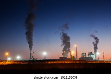 polluting thick smoke coming out of factory chimney at sunset - environment background