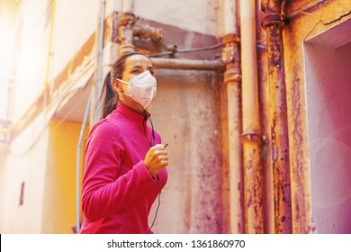 Pollution concept. Woman jogging while wearing protection mask