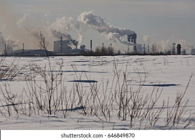 Pollution of the environment by a metallurgical plant. Pipes with smoke, carbon dioxide emissions into the atmosphere. Industrial winter landscape with a factory and fields.
