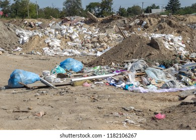 Pollution of the environment by people. Illegal garbage dump in the wasteland. A pile of household garbage in a dump in bags. A huge pile of waste extends to the garbage mountain