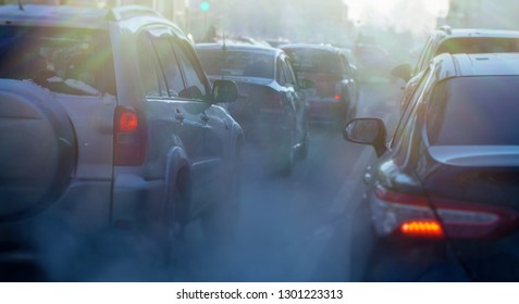pollution from the exhaust of cars in the city in the winter. Smoke from cars on a cold winter day