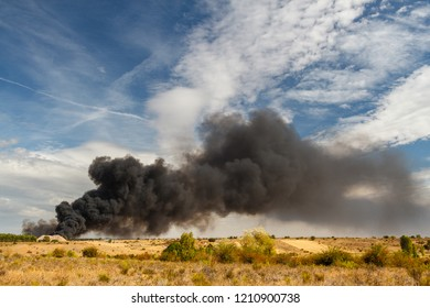 Pollution. Fire in a recycling plant and smoke column.