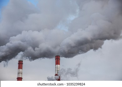 Pollution of the nature, pipes with gray smoke in the sky