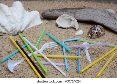 Pollution of plastic straws and fork left on beach background with beautiful seashells and drift wood.  Plastic pollution is harmful to  marine lives. Environmental concept. Ban single use plastic.