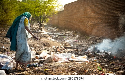 Pollution and poverty. Indian old female searching food in urban industrial garbage on 13 Feb, 2012. Kanpur, India