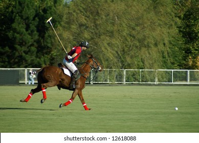 polo player in action about to hit the ball